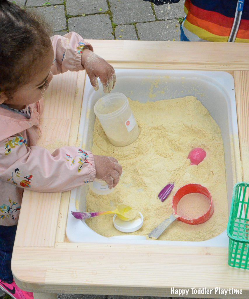 A toddler playing in baby cereal sensory table